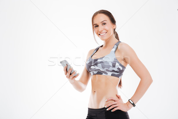 Young aerobic woman with phone Stock photo © deandrobot