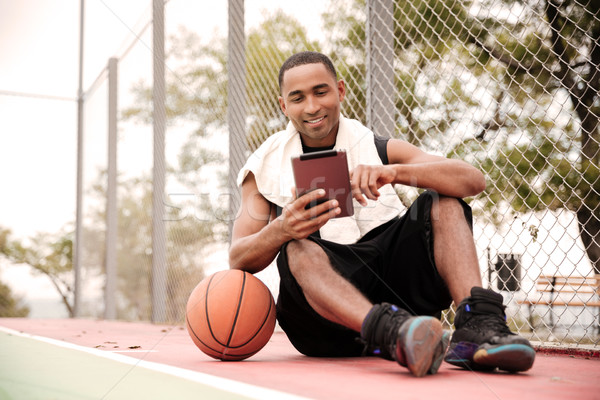 Happy african basketball player sitting in park and using tablet Stock photo © deandrobot