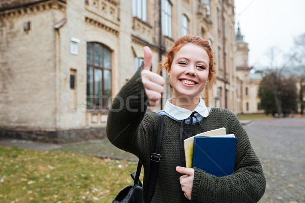 Glimlachend tevreden vrouwelijke student boeken Stockfoto © deandrobot