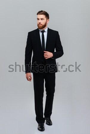 Uomo d'affari mani barbuto abito nero guardando Foto d'archivio © deandrobot