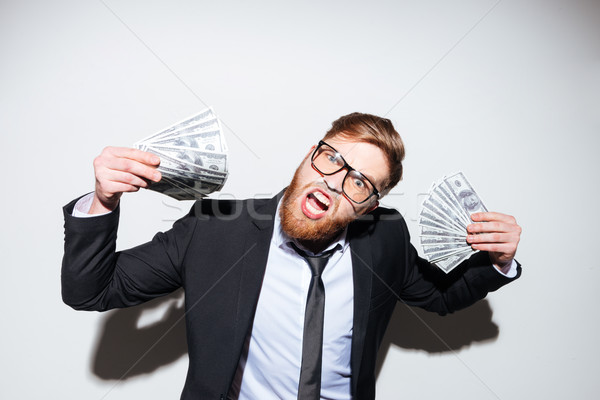 Happy business man with money in hands Stock photo © deandrobot