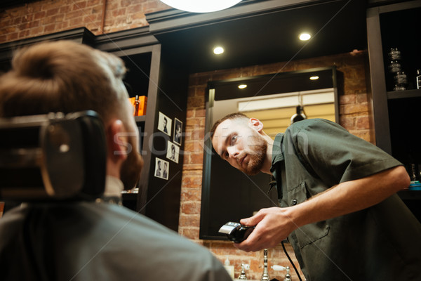 Young man getting beard haircut in barbershop Stock photo © deandrobot
