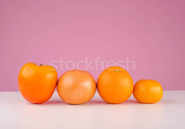 Fresh fruit mandarin, persimmon tangerine and orange on a table Stock photo © deandrobot