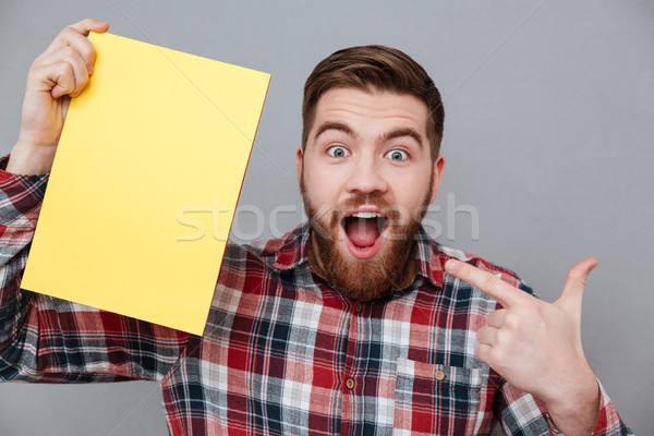 Bearded Surprised man in shirt holding blank board Stock photo © deandrobot