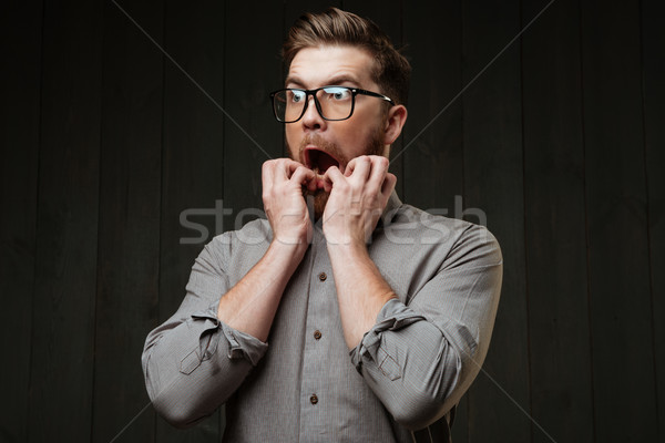 Portrait of a scared bearded man in eyeglasses looking away Stock photo © deandrobot