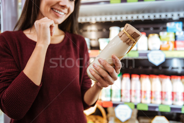 Happy woman choosing and buying yogurt in grocery shop Stock photo © deandrobot