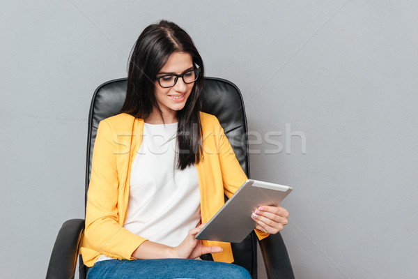 Cheerful woman sitting on office chair while using tablet computer Stock photo © deandrobot
