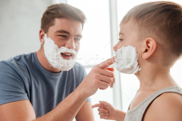 Bearded father and son applying shaving foam on their faces Stock photo © deandrobot