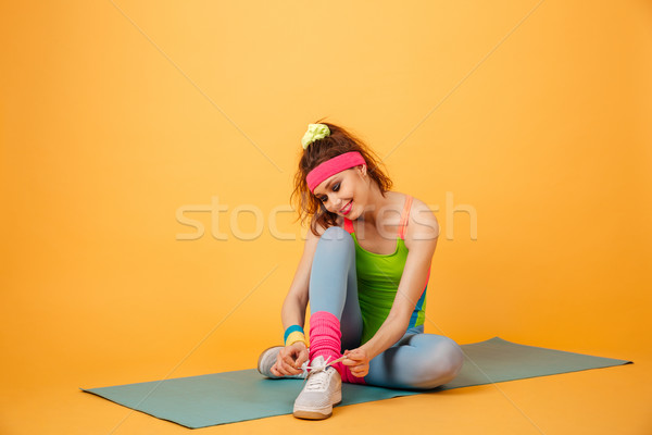 Happy charming young sportswoman sitting on mat and tying shoelaces Stock photo © deandrobot