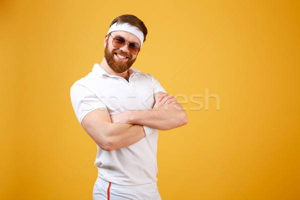 Smiling sportsman in sunglasses with crossed arms Stock photo © deandrobot