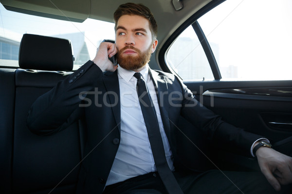 Handsome serious business man talking on mobile phone Stock photo © deandrobot