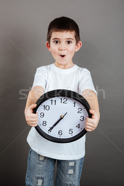 Stock photo: Surprised cute little boy standing and holding clock
