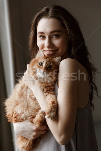 Vertical image of smiling woman in nightie with cat Stock photo © deandrobot
