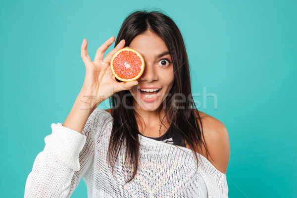 Cheerful amusing young woman covered her eye with grapefruit half Stock photo © deandrobot