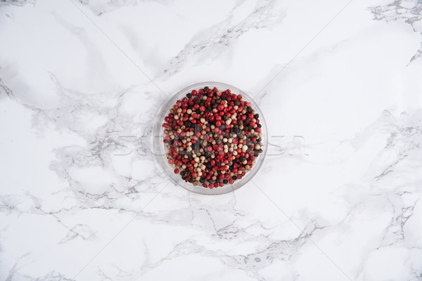 Top view of a bowl with various peppercorns seeds mix on white Stock photo © deandrobot