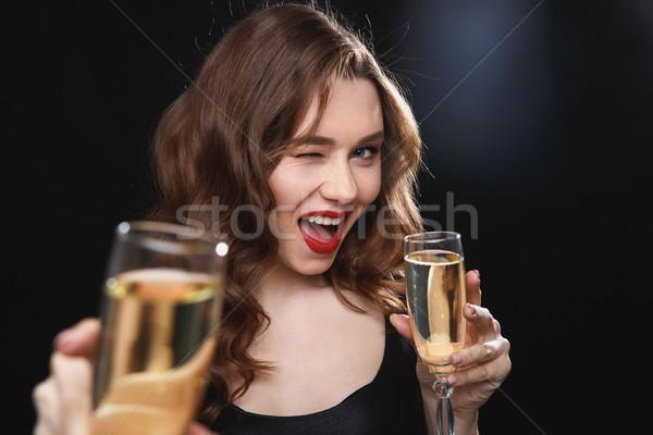 Derűs fiatal nő üveg pezsgő kacsintás bájos Stock fotó © deandrobot