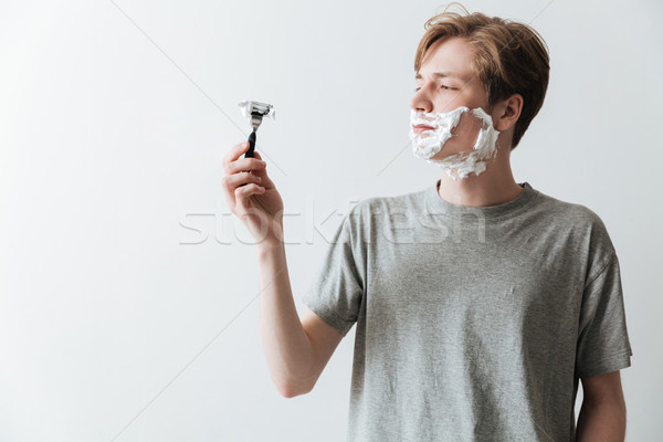 Young man in  shaving foam looking at razor Stock photo © deandrobot