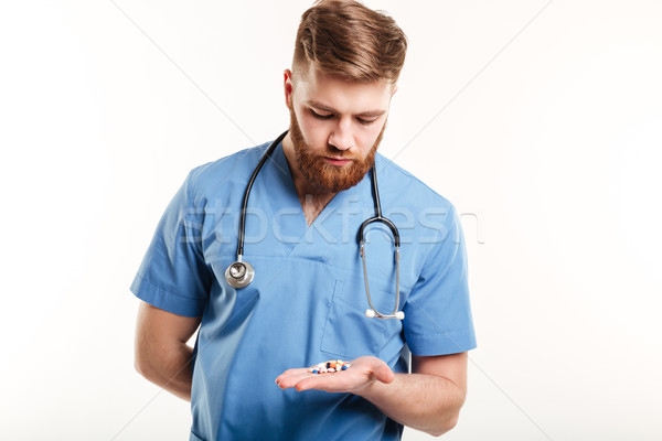 Doctor or nurse with stethoscope looking at pills in palm Stock photo © deandrobot