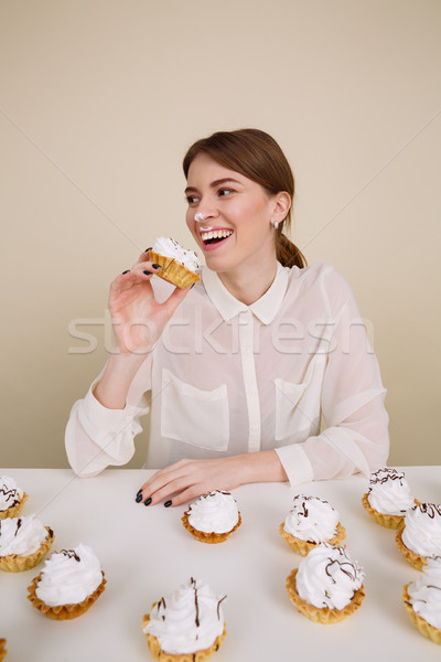Happy amusing young woman smiling and eating cakes Stock photo © deandrobot