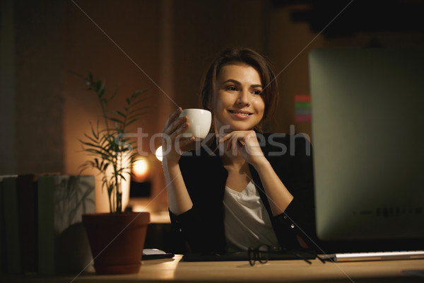 Stock photo: Happy young woman designer at night using computer