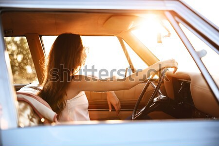 Side view of a young woman sitting inside a retro car Stock photo © deandrobot