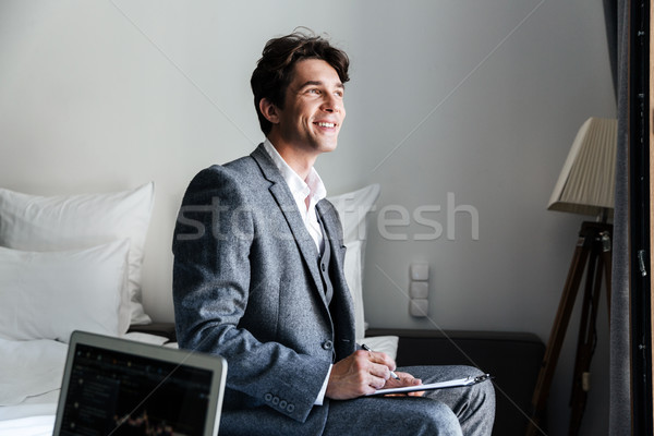 Handsome smiling male attorney reviewing some contracts Stock photo © deandrobot