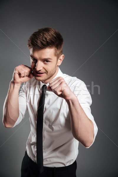 Confident young man in formalwear boxing Stock photo © deandrobot