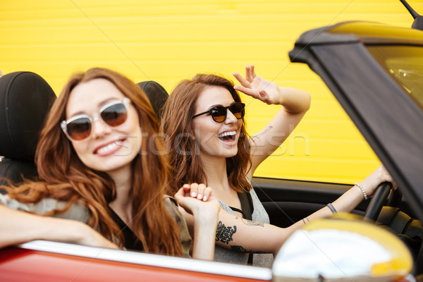Happy two women friends sitting in car over yellow wall. Stock photo © deandrobot