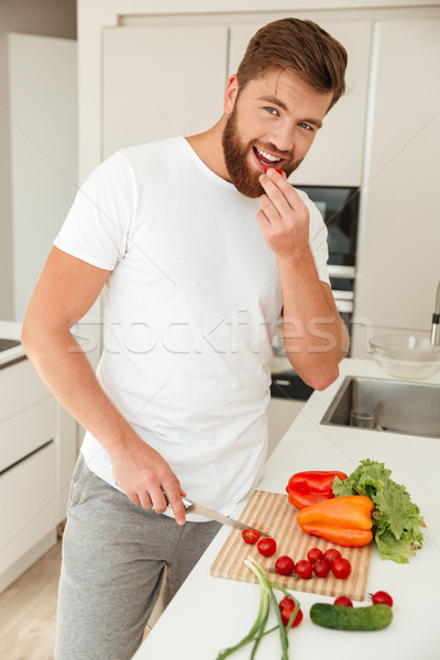 Vertical image of smiling bearded man standing near the table Stock photo © deandrobot