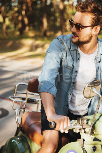 Handsome serious young bearded man sitting on scooter Stock photo © deandrobot