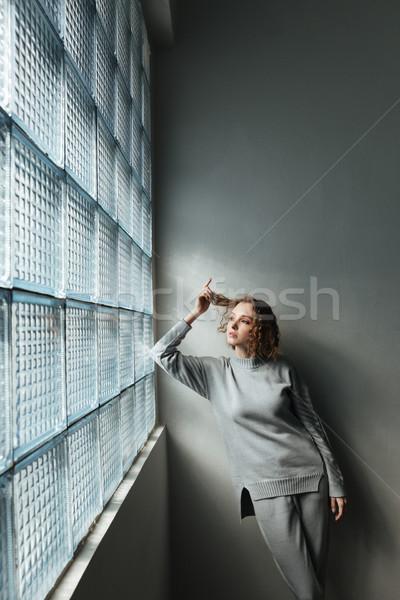 Fiatal nő néz ablak fiatal komoly nő Stock fotó © deandrobot