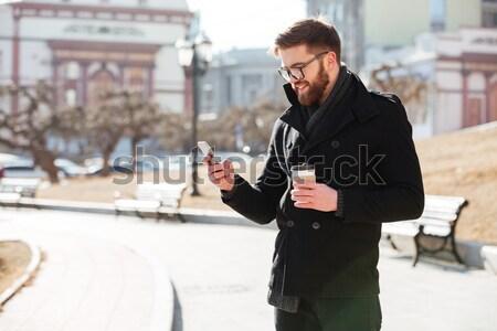 Przystojny młody człowiek kurtka patrząc telefonu komórkowego portret Zdjęcia stock © deandrobot