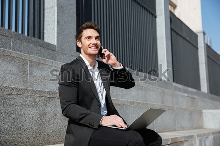Stock photo: Happy young businessman sitting outdoors talking by phone.