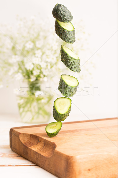 Sliced whole cucumber flying above a wooden chopping board Stock photo © deandrobot