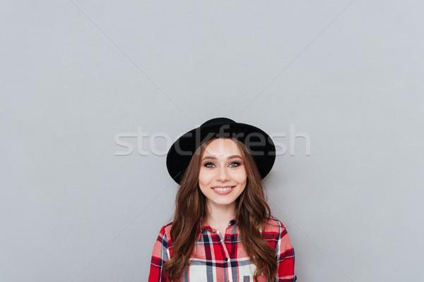 Pozitív lány kockás póló kalap néz Stock fotó © deandrobot