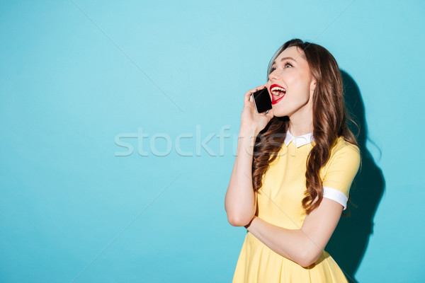 Pretty joyful girl in dress talking on mobile phone Stock photo © deandrobot