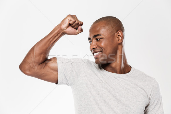 Cheerful young african man showing biceps. Stock photo © deandrobot
