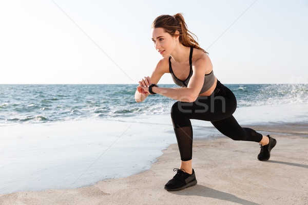 Portrait of young smiling  fitness woman checking time while doi Stock photo © deandrobot