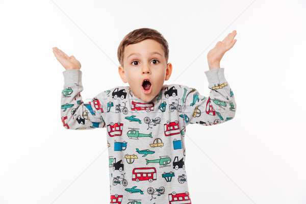 Portrait of a surprised little kid standing and shrugging shoulders Stock photo © deandrobot