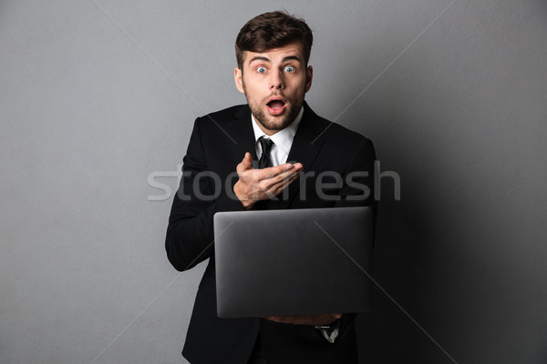 Amazed young guy in black suit holding laptop, looking at camera Stock photo © deandrobot