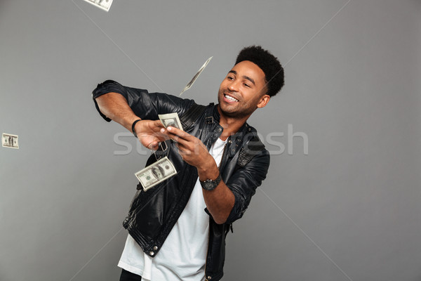 Funny afro american rich man scattering dollars banknotes Stock photo © deandrobot