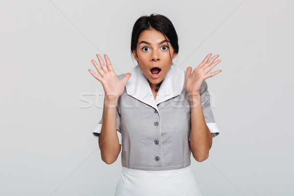 Close-up photo of amazed brunette maid in uniform standing with  Stock photo © deandrobot