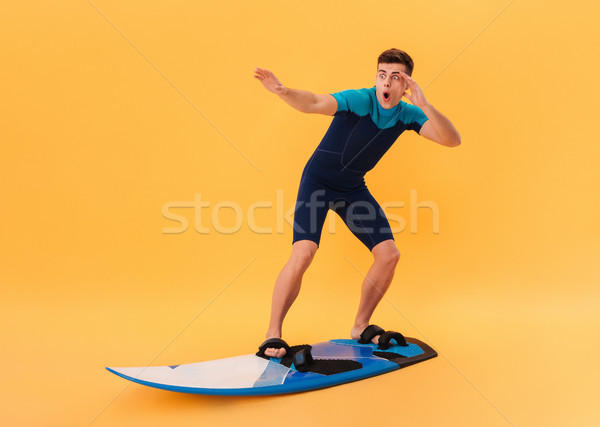 Image of Shocked surfer in wetsuit using surfboard Stock photo © deandrobot