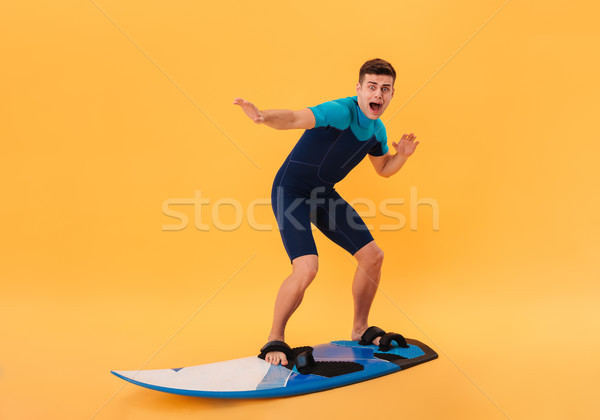 Image of Scared surfer in wetsuit using surfboard Stock photo © deandrobot