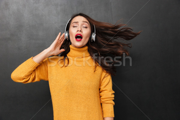 Carefree brunette woman in sweater and headphones listening music Stock photo © deandrobot