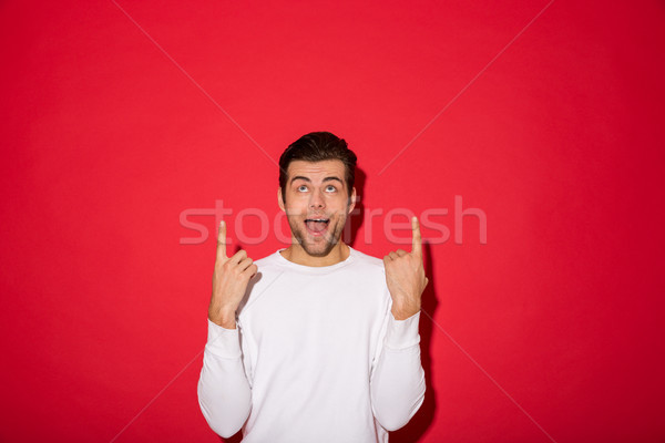 Shocked man pointing and looking up with open mouth Stock photo © deandrobot