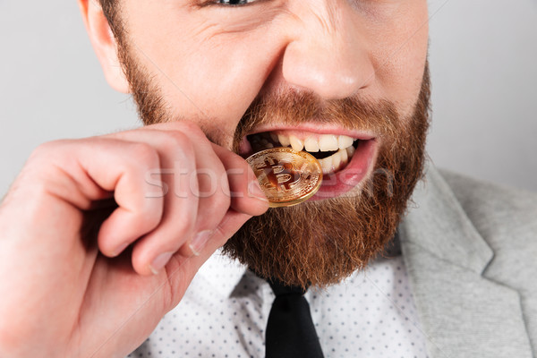 Close up portrait of a man biting golden bitcoin Stock photo © deandrobot