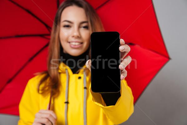 Közelkép portré mosolyog lány esőkabát néz Stock fotó © deandrobot
