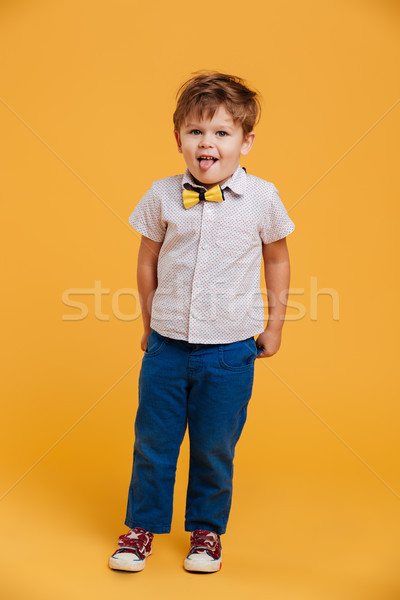 Little boy child standing isolated showing tongue. Stock photo © deandrobot