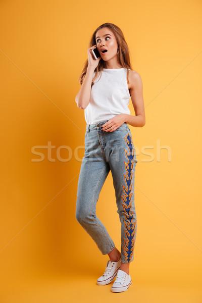 Full length portrait of a surprised pretty girl Stock photo © deandrobot